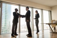 Boss shaking hand to new company worker in cabinet. Caucasian businessman with female company secretary welcoming with handshaking african american partner in Royalty Free Stock Image