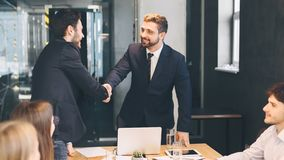 Boss shaking hands with business partner, finishing up meeting