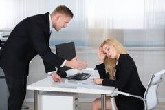 Boss Shouting At Employee que se sienta en el escritorio Foto de archivo libre de regalías