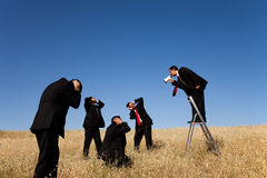 Boss shouting to his employees. Powerfull businessman shouting very loud at the megaphone to his employees Royalty Free Stock Photo