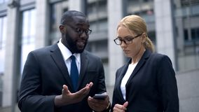 Boss showing female employee business diagrams in smartphone, new technology. Stock photo royalty free stock photography
