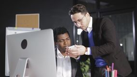Boss shows his employee a pictures on the smartphone in the office stock footage