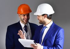 Boss shows project to engineer with cheerful face. Engineer and businessman discuss project. Happy employee and boss with helmets at meeting. Engineering Royalty Free Stock Photography