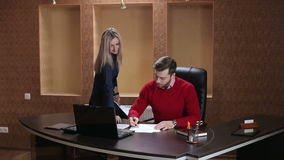 Boss signing document and talking to secretary. stock footage