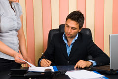 Boss signing secretary documents. Boss sitting on chair in office signing  his secretary documents,check also Business people Royalty Free Stock Image