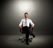 Boss sitting on chair. Successful boss sitting on chair against grey wall Stock Images
