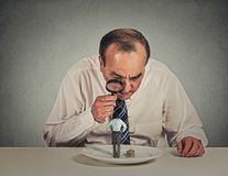 Boss skeptically looking at employee through magnifying glass Royalty Free Stock Photos