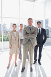 Boss standing with his arms folded with serious colleagues behind Stock Images