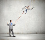 Boss and subordinate. Businessman holding on lead young colleague businesswoman Royalty Free Stock Image