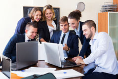 Boss with subordinate officials discussing. Adult boss with subordinate officials discussing long-term forecast and smiling Royalty Free Stock Image