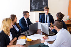 Boss with subordinate officials discussing. Happy boss with subordinate officials discussing long-term forecast and smiling Royalty Free Stock Image