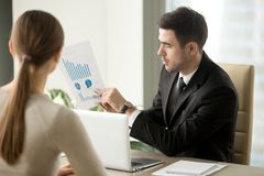 Boss talking about company financial perspectives. Male financial adviser showing document with profitability forecast to female client. Bank employee explaining Royalty Free Stock Image
