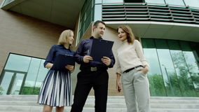 Boss and two secretaries. Boss and two female secretaries talking near the modern building stock video