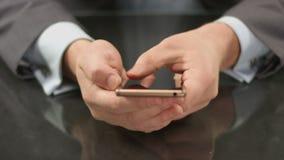 Boss usando smartphone costoso, manosea el primer de la pantalla táctil con los dedos almacen de metraje de vídeo