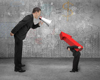 Boss using megaphone yelling at employee carrying red arrow sign. Boss using megaphone yelling at employee carrying big 3D red arrow sign with doodles wall and Royalty Free Stock Photo