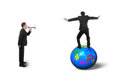 Boss using speaker yelling at businessman balancing on ball Royalty Free Stock Photo