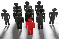 Boss vs leader concept. Crowd of human figures behind red Royalty Free Stock Photos