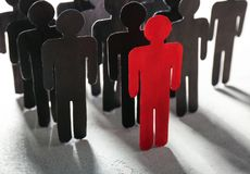 Boss vs leader concept. Crowd of human figures behind red. One on light background royalty free stock photo