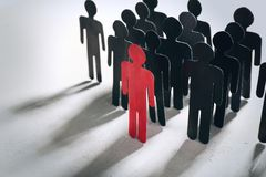 Boss vs leader concept. Crowd of human figures behind red one stock photo