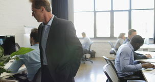 Boss walking in modern open office while group of business people working on computers, leader looking at mix race team