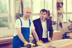Boss and worker in a carpenter`s workshop Royalty Free Stock Photo