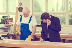 Boss and worker in a carpenter`s workshop Royalty Free Stock Image