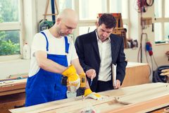Boss and worker in a carpenter`s workshop Stock Photo