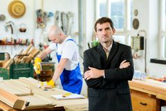 Boss and worker in a carpenter`s workshop Stock Image