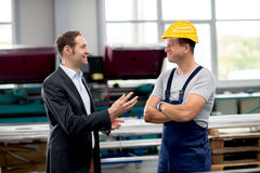 Boss and worker in conversation. Young boss and worker in conversation Royalty Free Stock Images