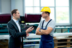 Boss and worker in factory. Young boss and worker in factory in conversation Stock Photos