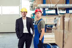 Boss and worker in stockroom. In the factory- young boss and worker in stockroom royalty free stock images