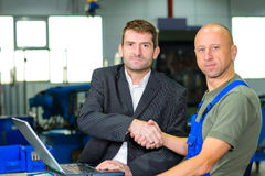 Boss and worker on work bench Royalty Free Stock Image