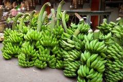 Bossen van groene bananen bij iIndia van de voedselmarkt stock foto's