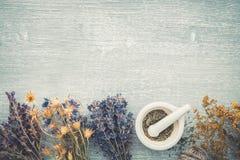 Bossen van het helen van kruiden en mortier op grijze houten plank royalty-vrije stock afbeeldingen
