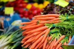 Bossen van wortelen op de markt die van de landbouwer worden verkocht Stock Afbeelding