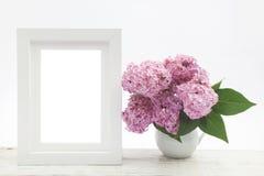 Bossering in vaas op houten lijst en witte kaderspot omhoog royalty-vrije stock afbeelding