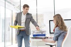 Bossy бизнесмен вручая папки к секретарше в офисе стоковая фотография rf