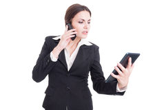 Bossy and busy young business woman using tablet and phone Royalty Free Stock Photography