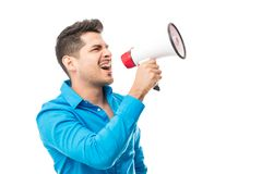 Bossy Man Shouting Into Megaphone Against White Background. Confident bossy man shouting into megaphone against white background royalty free stock image