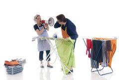 Bossy wife. Houseman ironing , being shouted at by wife Stock Photo
