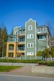 Bostads- byggnad för låg löneförhöjning på bakgrund för blå himmel Arkivfoto