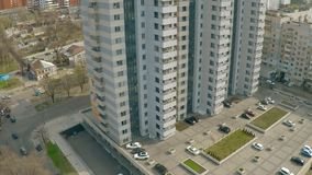 Bostads- byggnad med bilparkeringar och barnlekplatsen Fastighet som upprättar skottet arkivfilmer