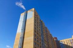 Bostads- byggnad med rör Utmärkt mot den blåa himlen Arkivbild