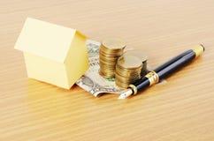 Bostadslånbegrepp med huspapper och reservoarpenna och dollar Arkivbild