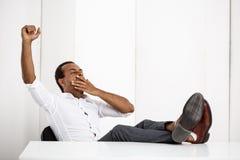 Bostezo africano acertado joven soñoliento del hombre de negocios, sentándose en el lugar de trabajo fotografía de archivo