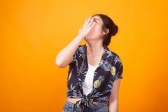 Bostezo asiático joven soñoliento de la mujer en camisa tropical fotografía de archivo