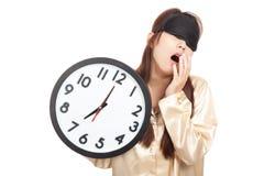 Bostezo asiático soñoliento de la muchacha con el control de la máscara de ojo un reloj Imagen de archivo libre de regalías