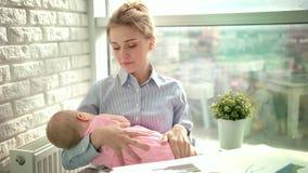 Bostezo cansado de la mujer con el niño durmiente en las manos Mamá soñolienta con el niño en el lugar de trabajo almacen de metraje de vídeo