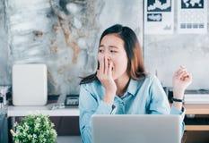 Bostezo casual asiático joven de la empresaria delante del cálculo del ordenador portátil imagenes de archivo