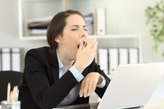 Bostezo ejecutivo cansado en la oficina imágenes de archivo libres de regalías